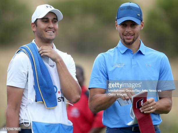 Golden State Warriors' Stephen Curry right and caddie Jonnie West stand on the 17th tee box in the first round of the Webcom Tour Ellie Mae Classic...