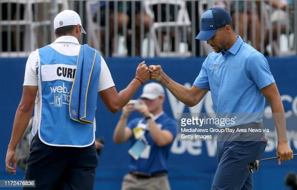 Golden State Warriors' Stephen Curry right gets a fist bump from caddie Jonnie West after making a par putt on the 18th green in the first round of...