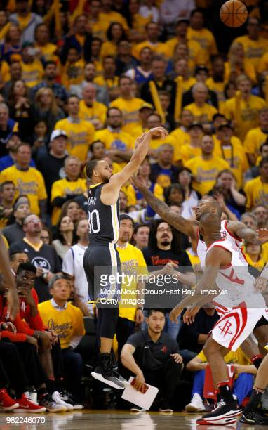 Golden State Warriors' Stephen Curry shoots a threepoint shot against Houston Rockets' Chris Paul and PJ Tucker in the third quarter of Game 4 of the...