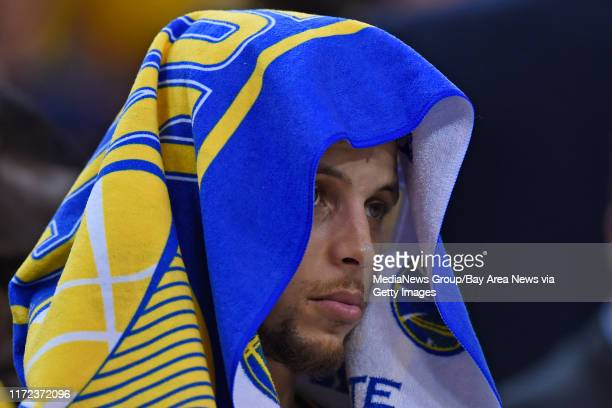 Golden State Warriors' Stephen Curry sits on the bench covered by a towel while playing the Oklahoma City Thunder in the second quarter of Game 1 of...