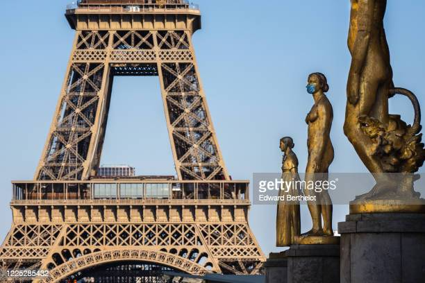 Golden statue is seen wearing a blue protective face mask at Trocadero, in front of the Eiffel Tower, on May 16, 2020 in Paris, France. The...
