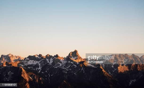 golden sun rays shining on snow covered mountainscape, bludenz, vorarlberg, austria - フォアアールベルク州 ストックフォトと画像