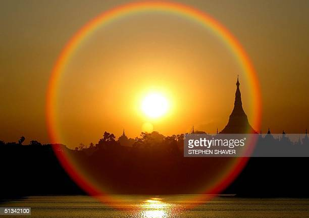 A golden sun sets near the Shwedagon temple as hyperfocal camera lens flare circles the massive stupa dominating Yangon's skyline 08 April 2002...