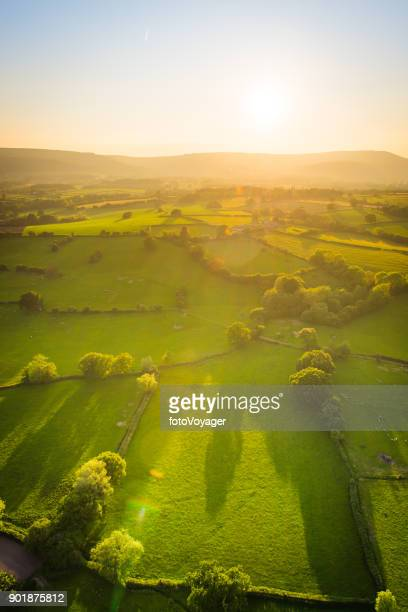 golden sunlight illuminating idyllic rural landscape green pasture aerial photograph - welsh culture stock pictures, royalty-free photos & images