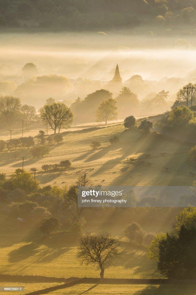 Golden sunrays through the mist with the Parish church of St Peter, Hope village. English Peak District. UK. : Stock Photo