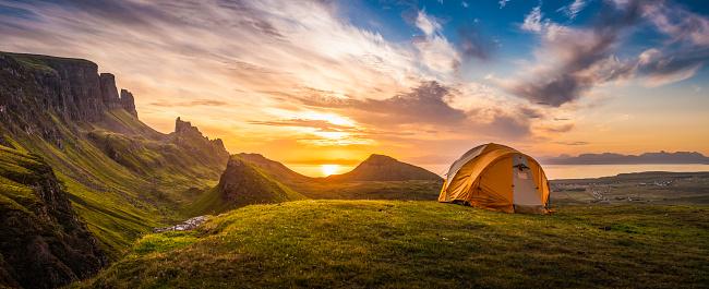 Golden sunrise illuminating tent camping dramatic mountain landscape panorama Scotland 526564828