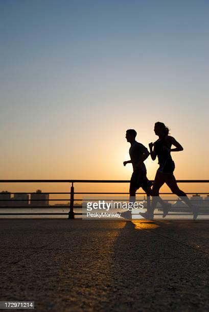 ゴールドの日の出ジョギングカップルのシルエット