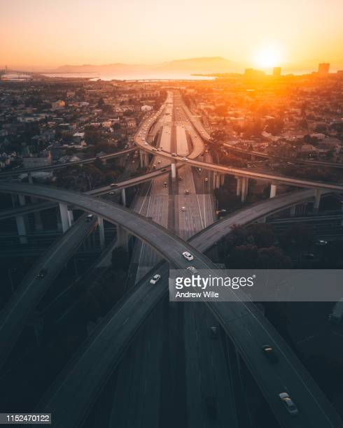 golden sunrise over a busy overpass in oakland, ca - oakland california skyline stock pictures, royalty-free photos & images
