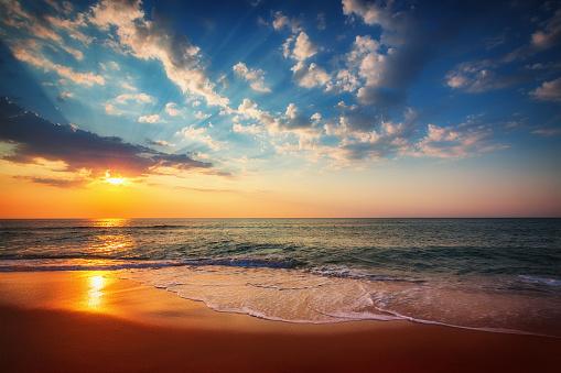 Golden sunrise over tropical beach 1090614484