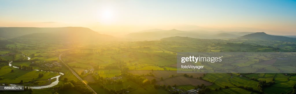 Golden sunset aerial panorama over idyllic green summer countryside mountains : Stock Photo