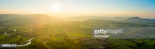 Golden sunset aerial panorama over idyllic green summer countryside mountains