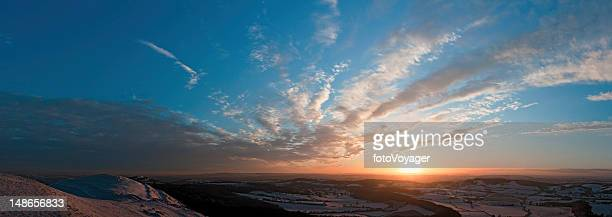 golden sunset idyllic winter landscape hills patchwork farms fields panorama - winter solstice stock photos and pictures