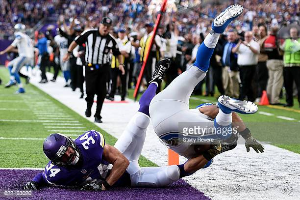 Golden Tate of the Detroit Lions leaps into the endzone in front of Andrew Sendejo of the Minnesota Vikings during a game at US Bank Stadium on...