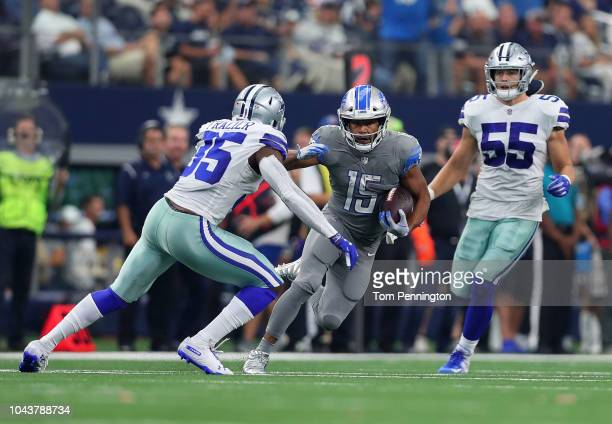 Golden Tate of the Detroit Lions runs the ball against Xavier Woods and Leighton Vander Esch of the Dallas Cowboys in the fourth quarter at ATT...