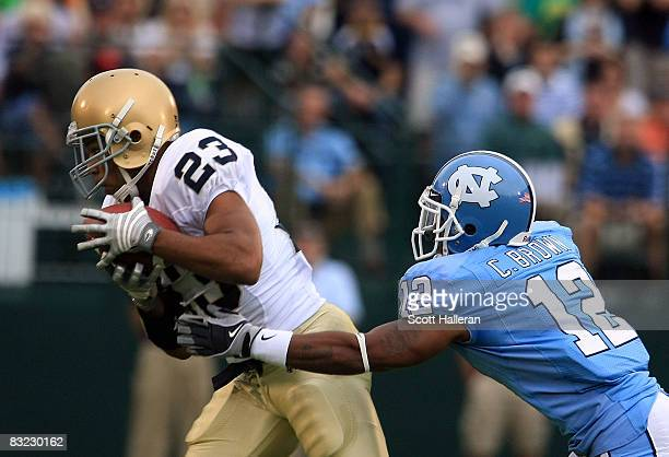 Golden Tate of the Notre Dame Fighting Irish catches a pass in front of Charles Brown of the North Carolina Tar Heels during the first half of their...