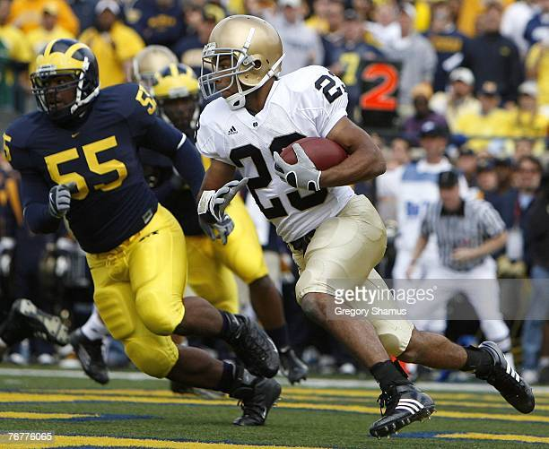 Golden Tate of the Notre Dame Fighting Irish tries to turn the corner in front of Brandon Graham of Michigan Wolverines at Michigan Stadium September...