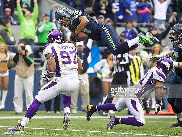 Golden Tate of the Seattle Seahawks goes airborne to score a touchdown in front of Everson Griffen of the Minnesota Vikings during a game at...