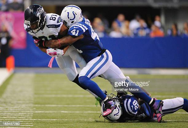 Golden Tate of the Seattle Seahawks is taken down by Antoine Bethea and Greg Toler of the Indianapolis Colts during a game at Lucas Oil Stadium on...