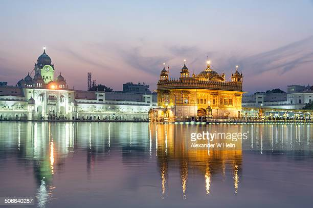 golden temple at dusk - golden temple india stock photos and pictures