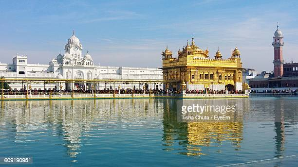 golden temple by river against sky in city - golden temple india stock photos and pictures