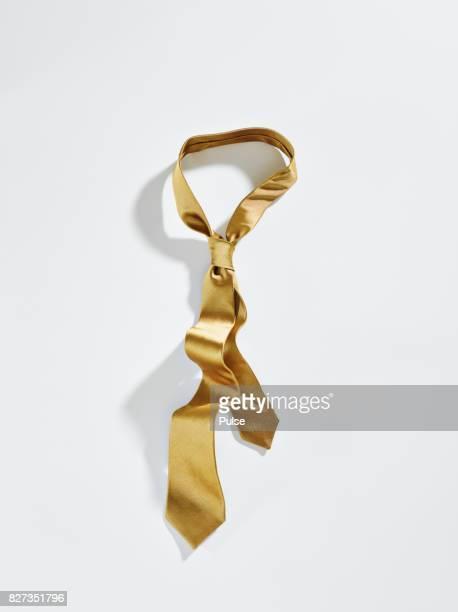 Golden tie on white background