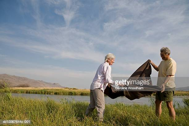 golden years couple in nature, unfolding picnic blanket - 65 69 years stock photos and pictures