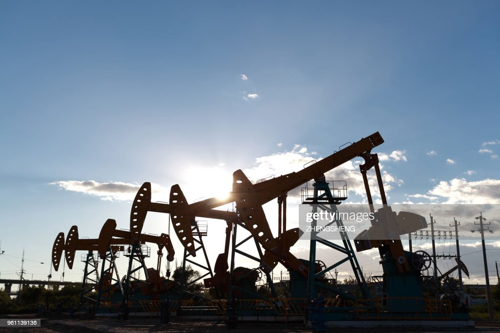 Golden yellow oil rig energy industry machine oil crude In the sunset backlighting : Stock Photo