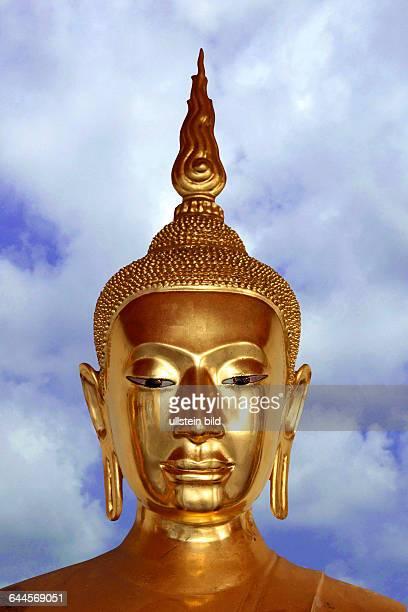 Goldener Buddha vor Wolkenhimmel