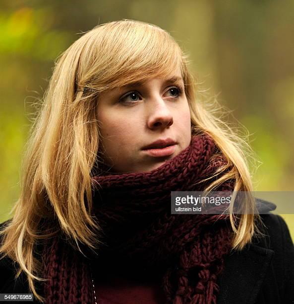 Goldener Herbst blonde junge Frau mit weinrotem Wollschal im Wald