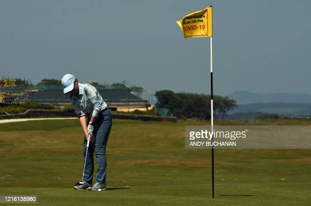 A golder putts on a green with a warning sign asking patrons not to touch the flag or pin to minimise the possibility of transmission of the novel...