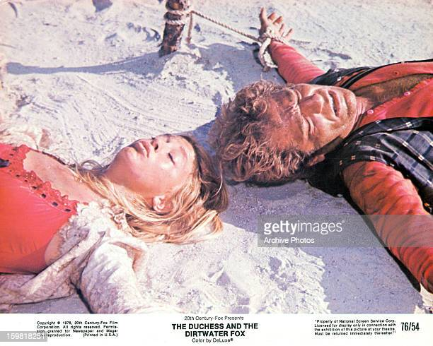 Goldie Hawn lies next to George Segal on the beach in a scene from the film 'The Duchess And The Dirtwater Fox', 1976.