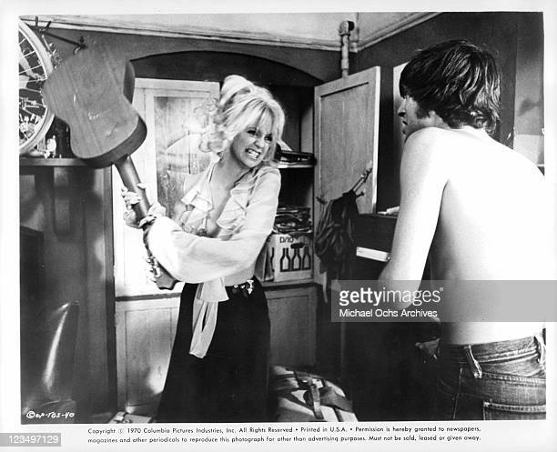 Goldie Hawn swings a guitar at Nicky Henson in a scene from the film 'There's A Girl In My Soup' 1970