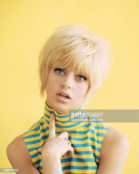 Goldie Hawn US actress wearing a blue and yellow striped sleeveless top in a studio portrait against a yellow background circa 1965