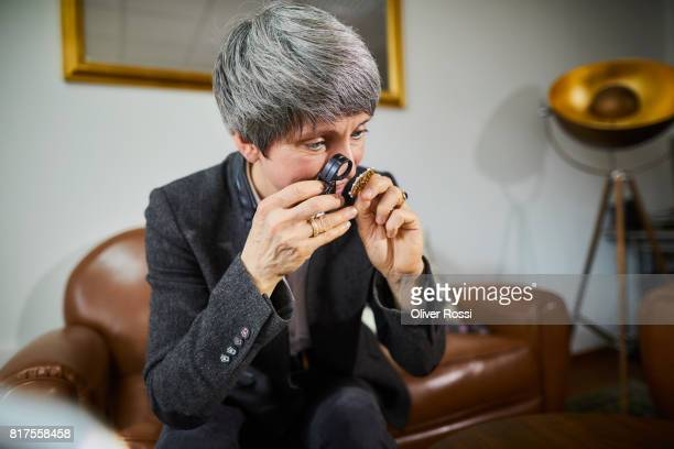Goldsmith examining piece of jewelry with a magnifying glass