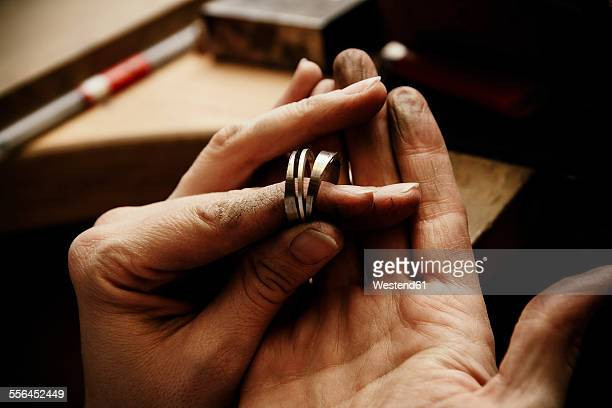 Goldsmith working on wedding rings, hand holding unfinished ring