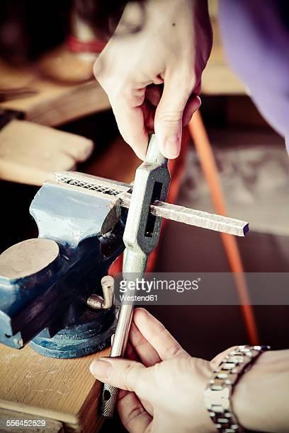 Goldsmith working on wedding rings in Mokume Gane style, preparing bench vice