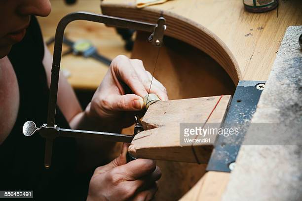 Goldsmith working with saw on wedding rings