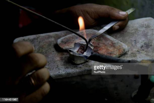Goldsmith works on gold ornaments at a workshop in Kolkata, India, August 27,2019. Gold prices in Indian markets remained steady today after rising...