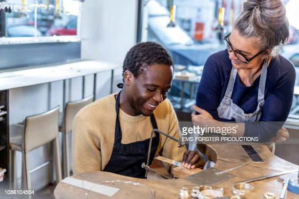 goldsmith workshop and retail shop led by independent master craftswoman with male apprentice of african origin - fugitive stock pictures, royalty-free photos & images