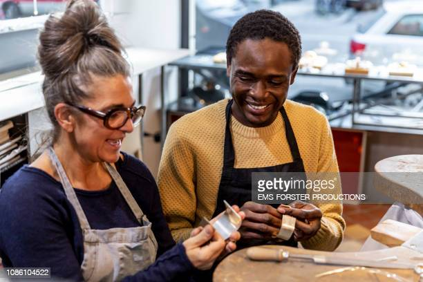 goldsmith workshop and retail shop led by independent master craftswoman with male apprentice of african origin - fugitive stock photos and pictures