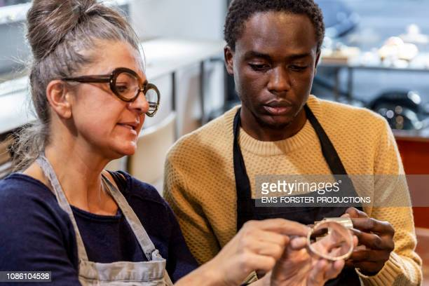 goldsmith workshop and retail shop led by independent master craftswoman with male apprentice of african origin - emigration and immigration stock-fotos und bilder