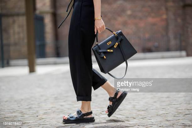 Golestaneh Mayer-Uellner is seen wearing black padded muscle shirt Frankie Shop, black paperbag pants 3.1 Phillip Lim, black Dad sandals Chanel,...