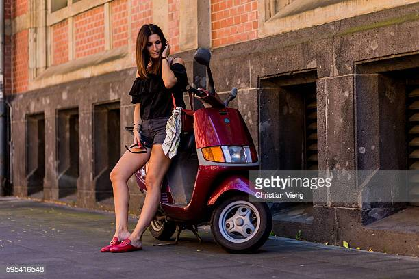 Golestaneh MayerUellner sitting on a red vespa wearing a black ruffled off shoulder top Carmen high waist denim shorts from Weekday red Princetown...