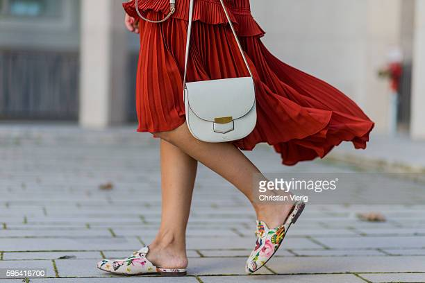 Golestaneh MayerUellner wearing a red plissee dress with ruffles from Self Portrait Canvas Princetown slipper with floral print from Gucci Garden...
