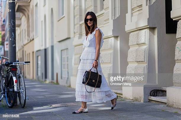 Golestaneh MayerUellner wearing a white lace dress with ruffles from Self Portrait flat sandals with pearls from Chanel black handle bag from Chanel...