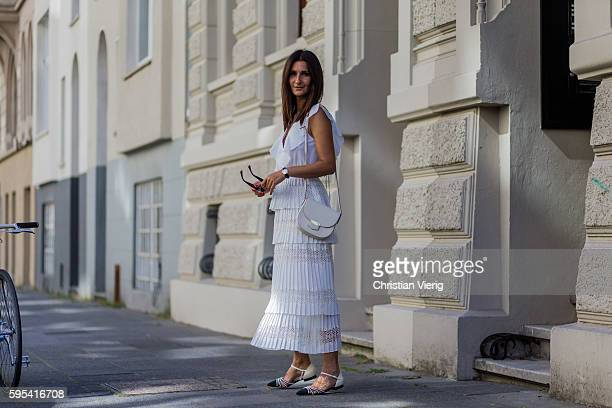 Golestaneh MayerUellner wearing a white lace dress with ruffles from Self Portrait flat sandals with pearls from Chanel white trotteur bag from...