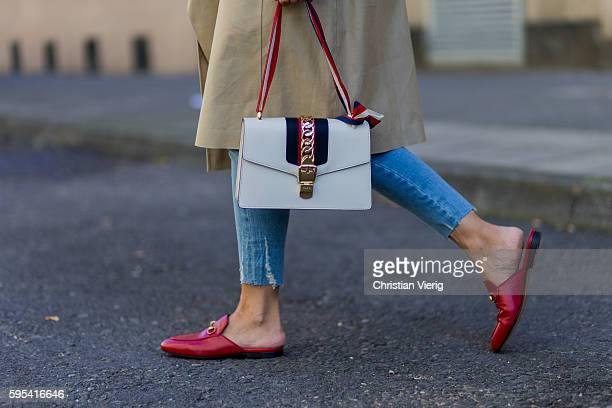 Golestaneh MayerUellner wearing an oversized beige Celine trench coat a cropped blue skinny jeans from Zara red Princetown leather slipper from Gucci...