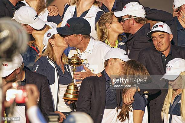41st Ryder Cup Team USA Davis Love III victorious holding trophy and kissing wife Robin JB Holmes kissing wife Erica and Jordan Spieth kissing...