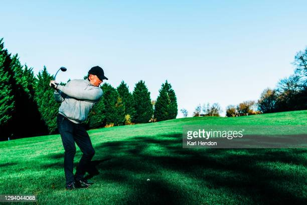 golf, a male golfer playing a shot on a winter's day - stock photo - golf stock pictures, royalty-free photos & images