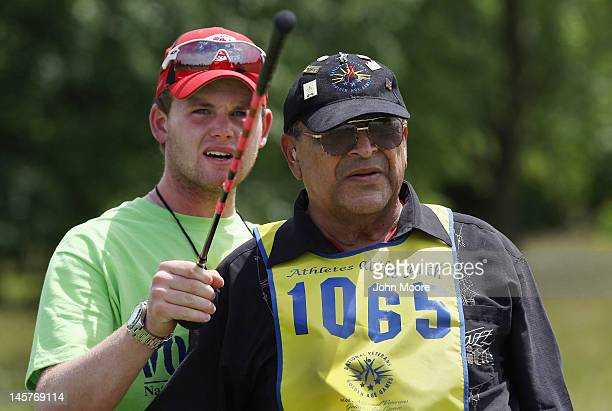 Golf assistant Alex Doneff helps visually impared military veteran Ray Trevino with a fareway shot during the golf competition of the National Golden...